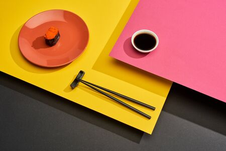 fresh maki with red caviar on plate near chopsticks and soy sauce on pink, yellow and black surface