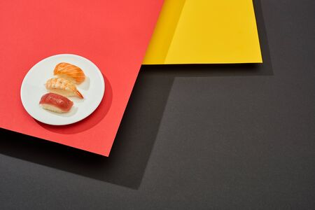 fresh nigiri with salmon, shrimp and tuna on red, yellow and black surface Фото со стока