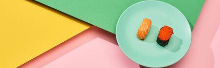 fresh nigiri with salmon and red caviar on yellow, pink, green background, panoramic shot