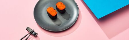 fresh nigiri with red caviar near chopsticks on blue, pink background, panoramic shot