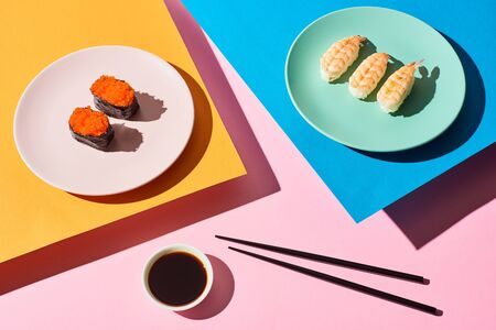 top view of fresh nigiri with shrimps and red caviar near soy sauce and chopsticks on blue, pink, orange background