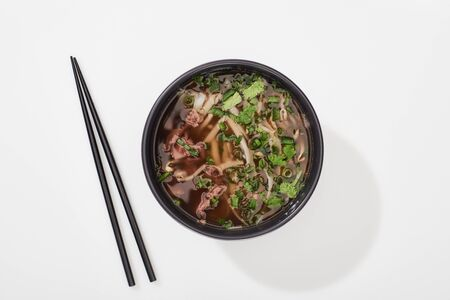top view of pho in bowl near chopsticks on white background