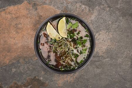 top view of pho in bowl with lime and coriander on stone background