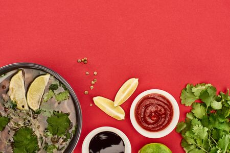 top view of pho in bowl near lime, chili and soy sauces and coriander on red background