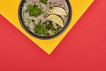 top view of pho in bowl with lime and coriander on red and yellow background