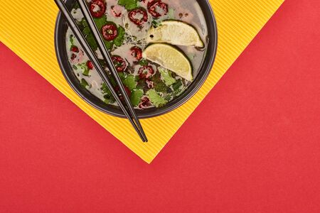 top view of pho in bowl with chopsticks, lime, chili and coriander on red and yellow background