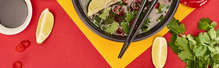 top view of pho in bowl with chopsticks near soy sauce, lime, chili and coriander on red and yellow background, panoramic shot