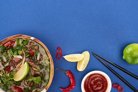top view of pho in bowl near chopsticks, lime, chili sauce on blue background