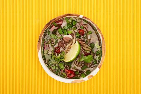 top view of pho in bowl on yellow textured background