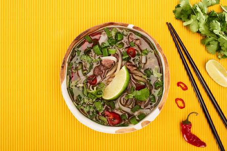 top view of pho in bowl near chopsticks, lime, chili and coriander on yellow textured background