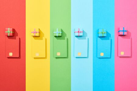 top view of multicolored empty credit cards and gift boxes on rainbow background Stockfoto