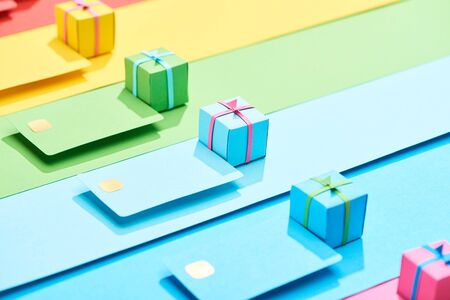 multicolored empty credit cards and gift boxes on rainbow background