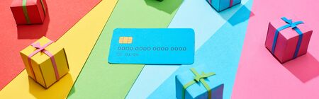 empty credit card and multicolored gift boxes on rainbow background, panoramic shot