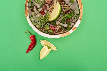 top view of pho in bowl near lime, chili on green background