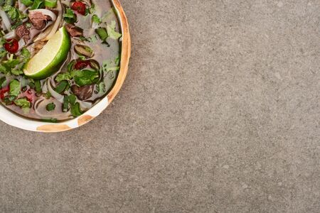 top view of pho in bowl on grey background