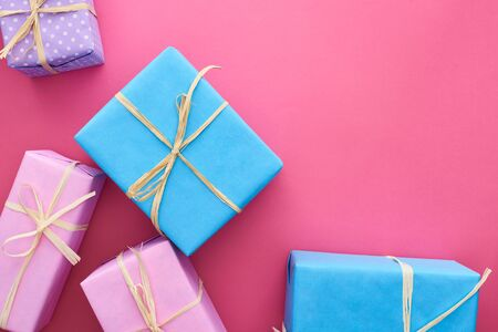 top view of colorful gifts with bows on crimson