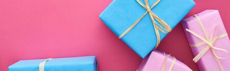panoramic shot of blue and pink presents on crimson  Stock Photo