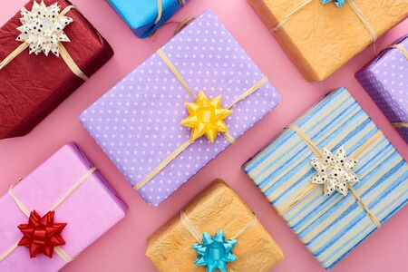 top view of colorful and wrapped gift boxes with bows on pink Reklamní fotografie
