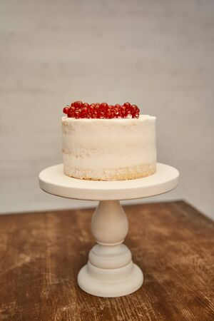 Sponge cake with cream decorated with redcurrant bunches on cake stand