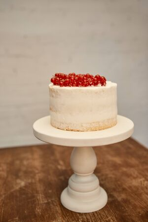 Sweet sponge cake with cream and juicy redcurrant on cake stand on wooden table Imagens