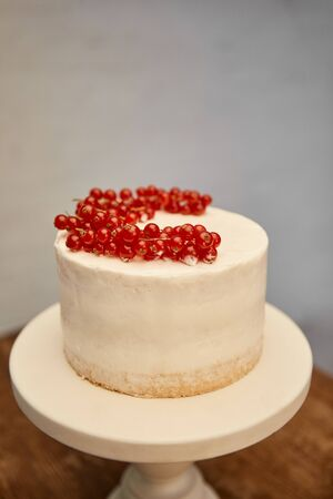 Tasty sponge cake with cream and fresh redcurrant on cake stand