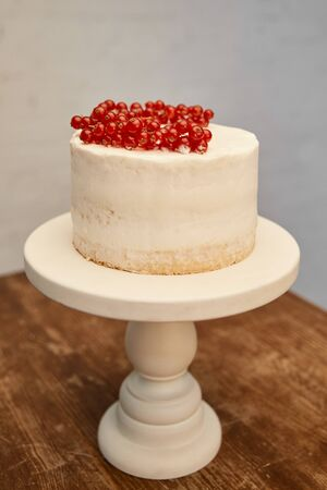 Tasty biscuit with ripe bunches of redcurrant on cake stand