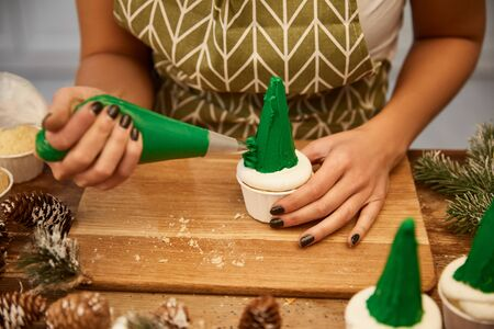 Cropped view of confectioner decorating cupcakes with cream beside pine cones on table Stockfoto