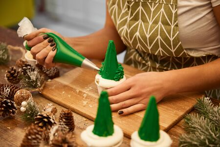 Cropped view of confectioner adding green cream on Christmas tree cupcakes beside spruce cones on table