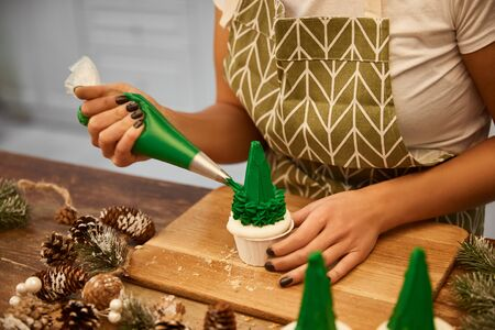Cropped view of confectioner adding tasty cream on Christmas tree cupcakes with spruce cones on wooden table Stockfoto