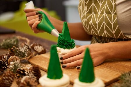 Selective focus of confectioner decorating tasty Christmas tree cupcakes beside spruce cones on table, cropped view