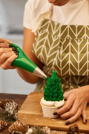 Cropped view of confectioner with pastry bag decorating Christmas tree cupcake on table with spruce cones