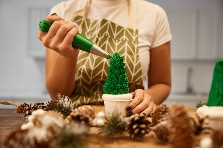 Cropped view of confectioner decorating Christmas tree cupcake with green cream beside spruce cones on table