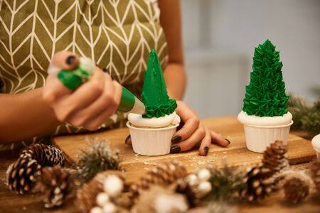 Selective focus of confectioner working with Christmas tree cupcakes beside spruce cones on table, cropped view  Stockfoto