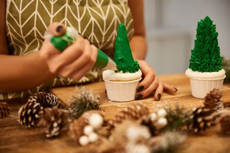 Cropped view of confectioner making Christmas tree cupcakes with green cream with spruce cones on table Stockfoto