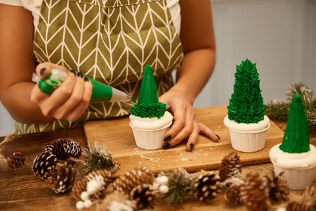 Cropped view of confectioner making Christmas tree cupcakes with green sweet cream beside spruce cones on table Stockfoto