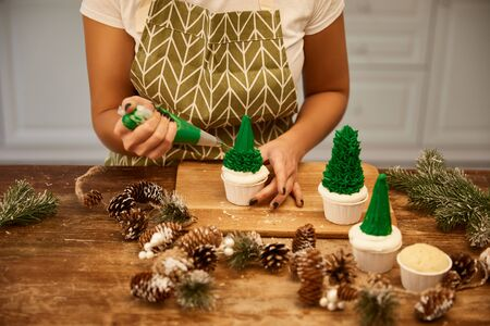 Cropped view of confectioner making Christmas tree cupcakes with cream beside spruce branches and cones on table
