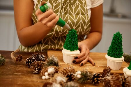 Cropped view of confectioner adding green sweet cream on Christmas tree cupcakes with spruce cones on table Stockfoto