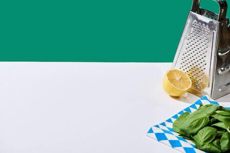lemon, basil leaves and grater on white table isolated on green Standard-Bild