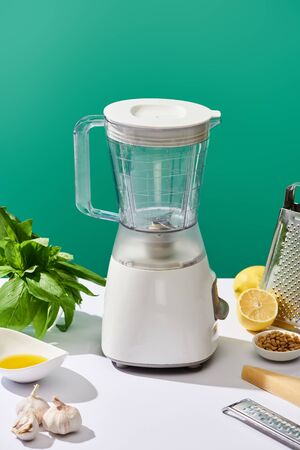 pesto sauce raw ingredients and food processor on white table isolated on green Standard-Bild