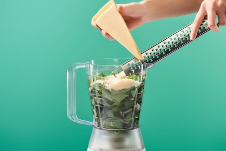 cropped view of woman grating Parmesan in food processor with basil leaves isolated on green