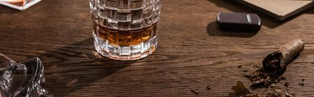 Glass of brandy with cigar, lighter and book on wooden table, panoramic shot