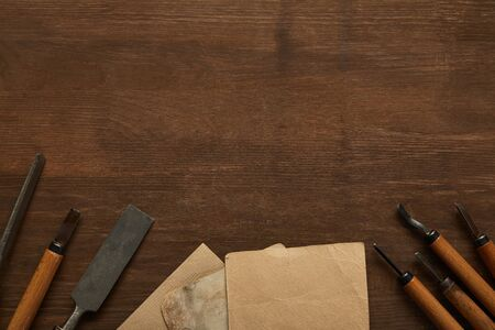 top view of aged carpentry tools near blank vintage papers on wooden table
