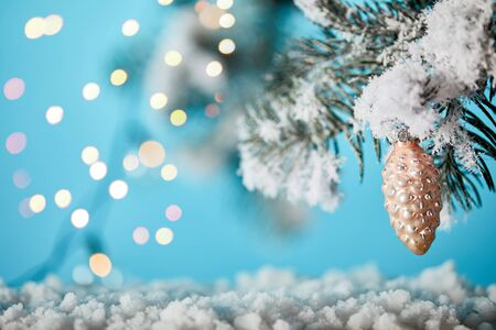 spruce branches in snow with christmas ball pine cone and lights bokeh on blue