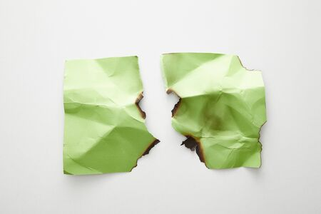 top view of empty crumpled, torn and burnt green paper on white background