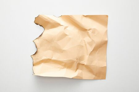 top view of empty crumpled and burnt beige vintage paper on white background