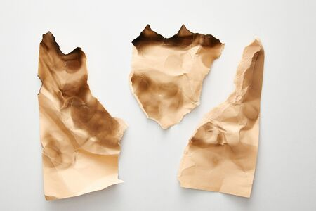 top view of empty crumpled and burnt beige vintage paper pieces on white background 版權商用圖片