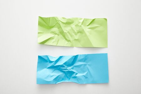 top view of empty crumpled blue and green paper on white background