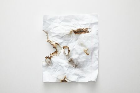 top view of empty crumpled and burnt vintage paper on white background