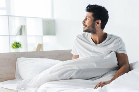 handsome and smiling bi-racial man looking away in morning