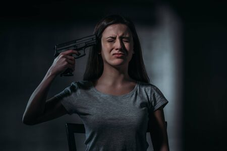 crying, despaired woman holding gun near chin on dark background Banco de Imagens